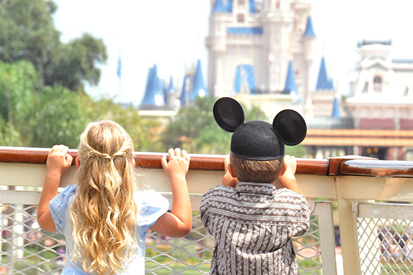 A young girl dressed as Cinderella and her brother, wearing a mouse-ear hat, gaze at Cinderella's Castle.