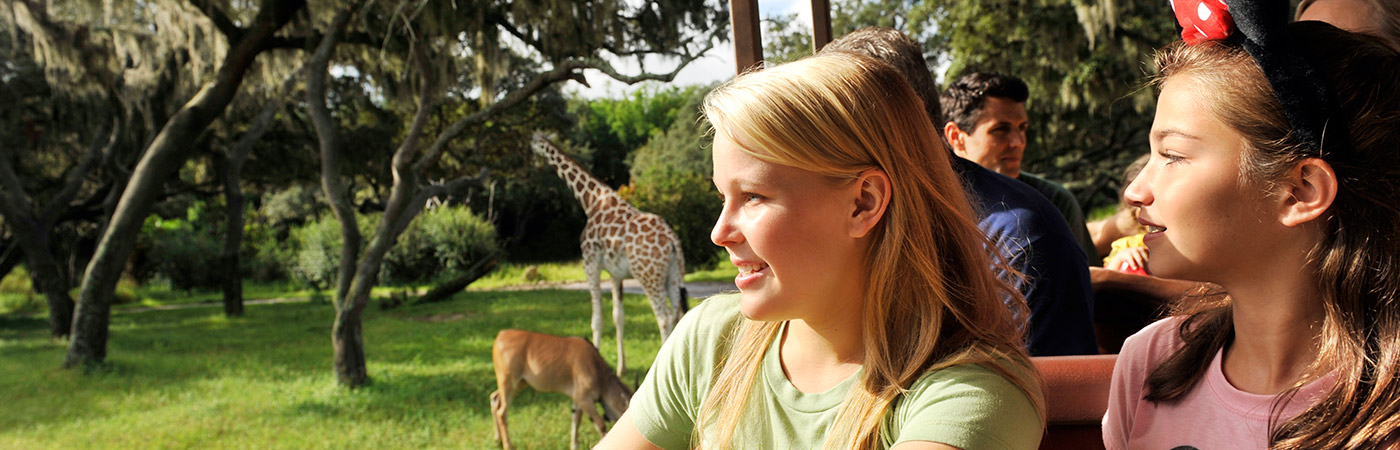Two young girls, one wearing Minnie Mouse Ears, enjoy looking at giraffes while riding enjoying Kilimanjaro Safaris.